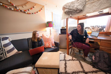 Two female students chatting in their room.