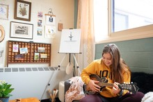 Female student playing guitar.