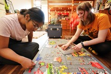 Two female students working on a puzzle.