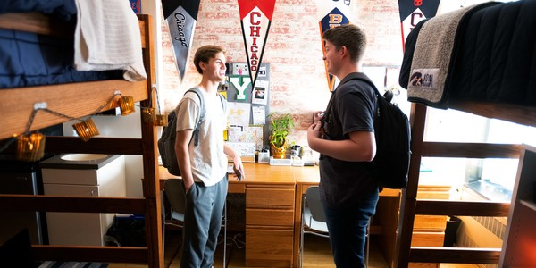 Two male students chatting in their room.