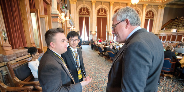 Two men talking with a senator at the state capitol house