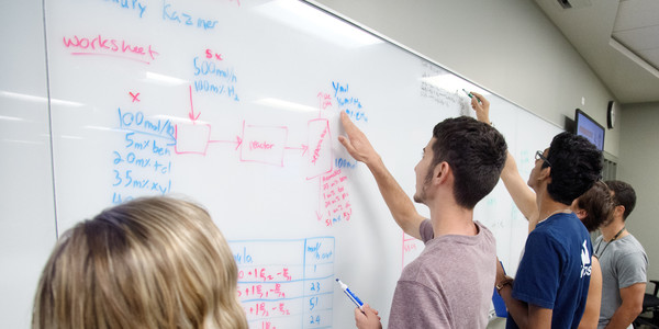 Students writing on white board